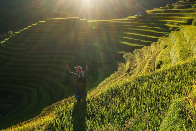 Undefined vietnamese hmong children showing the hand in rice terrace when the sunset time with lens