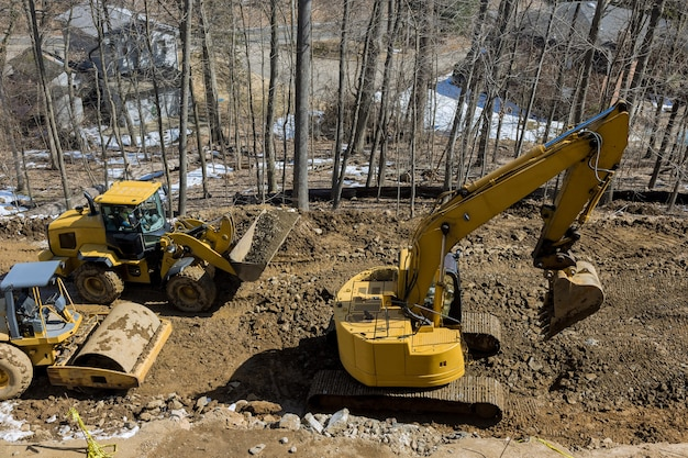 新しいアスファルト道路の建設中。新しい道路建設現場で作業している掘削機、グレーダー、ロードローラー