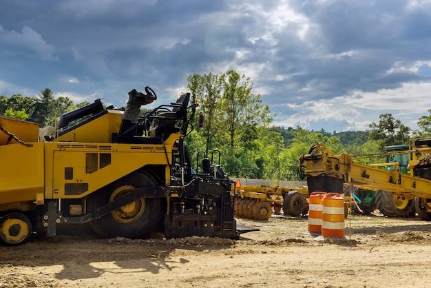 新しいアスファルト道路の建設中。新しい道路で作業している掘削機、グレーダー