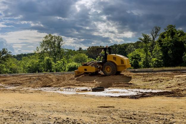 Строятся новые дорожные экскаваторы, грейдеры и дорожные работы на стройплощадке.
