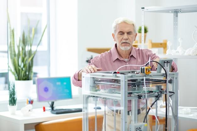 制御下。 3dプリンターの仕事を見て、メカニズムの内部を覗く白髪の老人