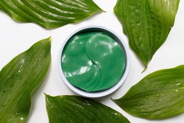 눈 패치 아래. 녹색 잎 사이에 화장품 콜라겐 하이드로겔 패치. 눈 밑 리프팅 주름 방지 마스크. 스킨케어 개념입니다.