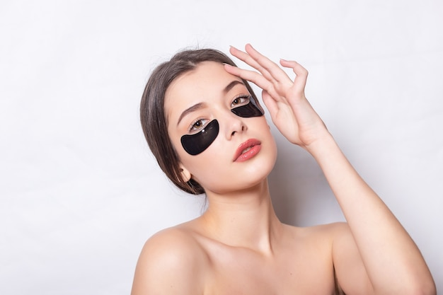 Черная заплатка под кожей вокруг глаз. крупным планом лицо красивой молодой женщины с увлажняющей коллагеновой маской подушечкой на здоровой свежей коже лица на белом фоне