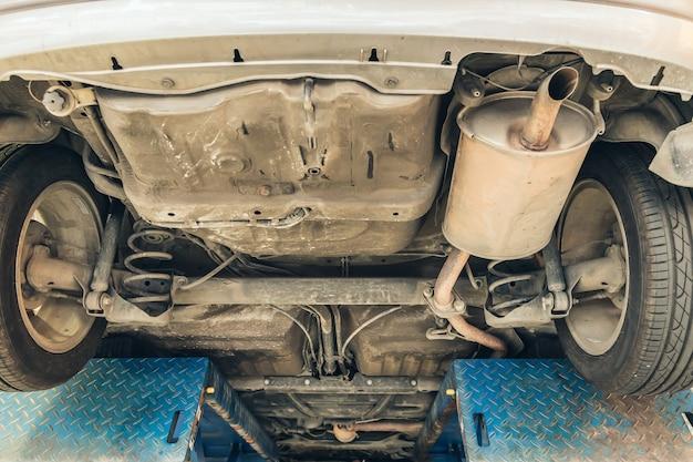 Под старый автомобиль крупным планом подвеска заднего колеса и глушитель глушителя выхлопной камеры грязный ремонт в гараже.
