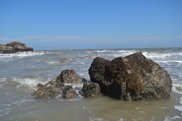 푸른 하늘 아래 파도가 해변의 바위를 두드리고