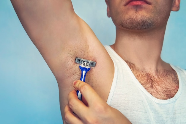 Underarm hair removal. male depilation. young attractive muscular man using razor to remove hair from his body. the self-care concept. epilation.