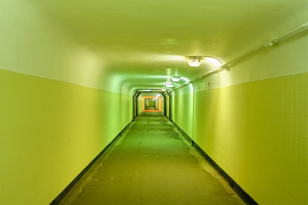 Underground pedestrian tunnel with green walls.