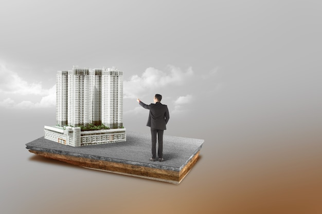 Underground soil layer of cross-section earth asian businessman pointing modern building on the street