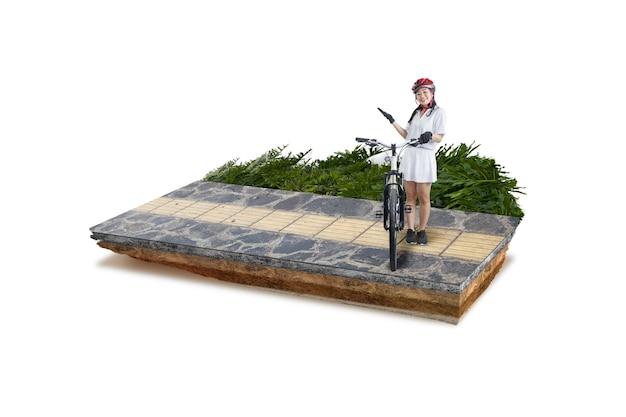 歩道で自転車の横に立っている自転車のヘルメットを持つアジアの女性と断面地球の地下土壌層