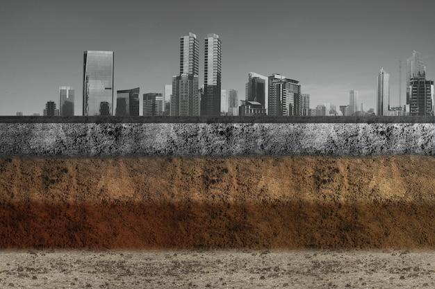 都市景観の背景を持つ上部にコンクリートを備えた断面地球の地下土壌層