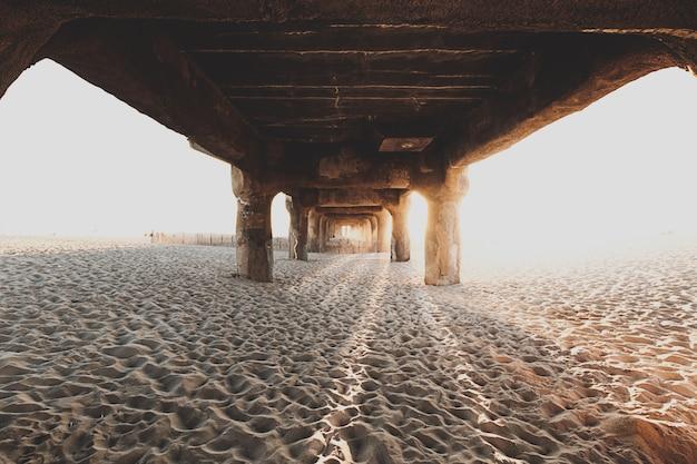 모래 해변에서 나무 다리 아래