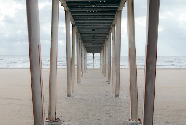Underneath of a wooden pier at the sandy beach on a cloudy day