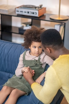 Understanding. dark-skinned dad sitting down near sofa holding hand of sad little curly-haired daughter looking attentively