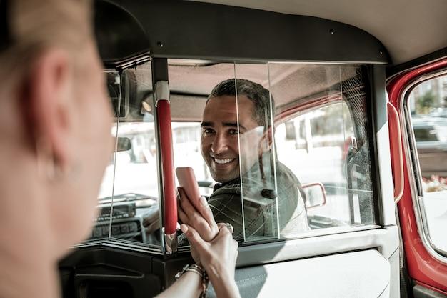 서로 이해하기. 자동차 운전사는 뒷좌석에 있는 여성을 뒤돌아보고 스마트폰을 보여주며 미소를 짓고 있습니다.