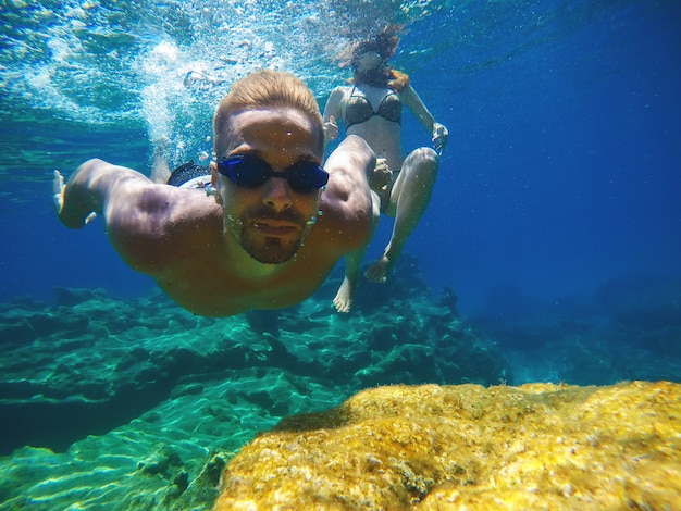 Underwater close photo of a young playful love couple swimming in the turquoise exotic sea for summer vacation.