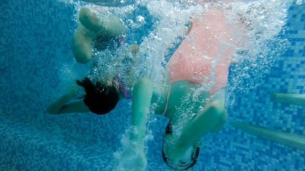 Подводное изображение двух девочек-подростков, прыгающих и ныряющих в бассейне в тренажерном зале
