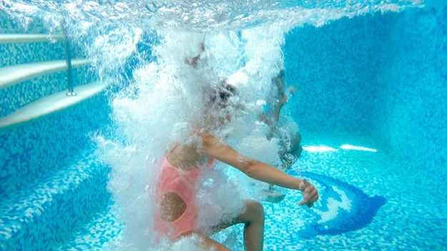 Underwater image of two teenage girl jumping and diving in swimming pool at gym