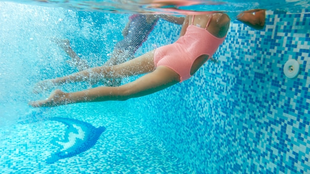 Underwater image of two teenage girls diving and swimming underwater at swimming pool