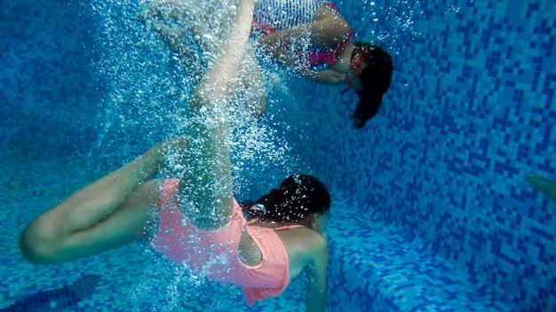 Underwater image of two teenage girls jumping in swimming pool at summer hotel resort