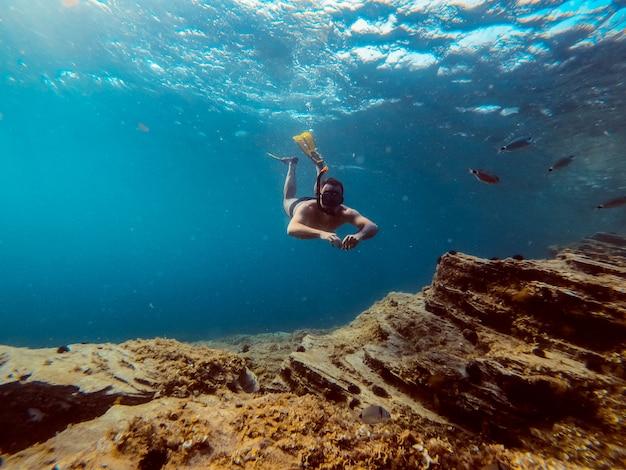 Underwater photo of men diver snorkeling in the sea water