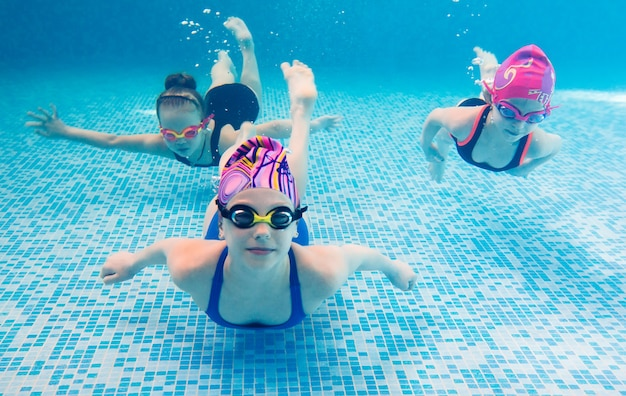 Underwater photo of young friends in swimming pool.