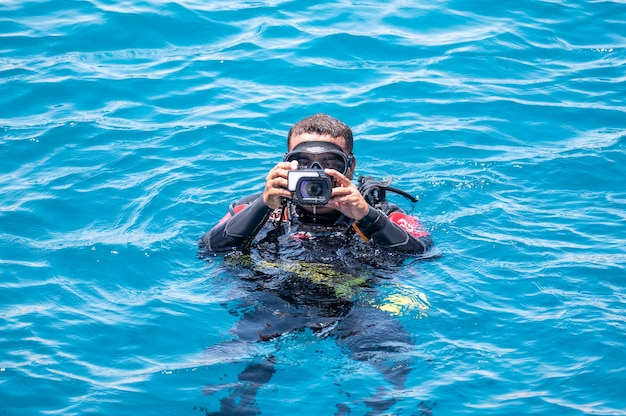 Underwater photographer videographer scuba dives on surface of the sea underwater photography