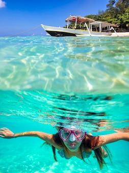Подводный портрет молодой женщины, ныряющей с маской и трубкой в океане.