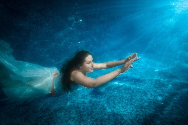 Underwater shot of beautiful woman in dress comes up from pool at beam of light