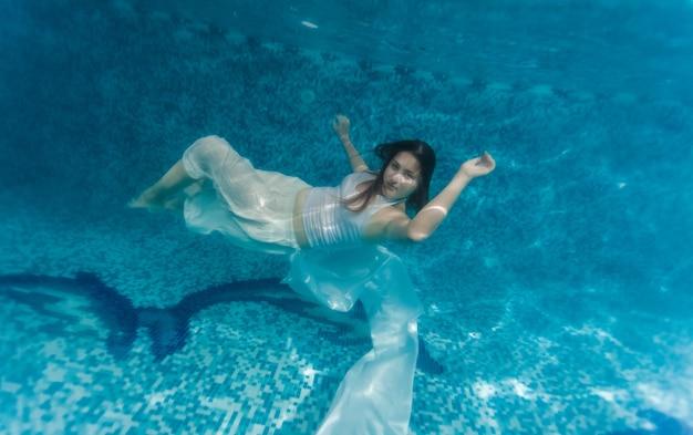 Подводный снимок женщины в белой ткани, плавающей под водой