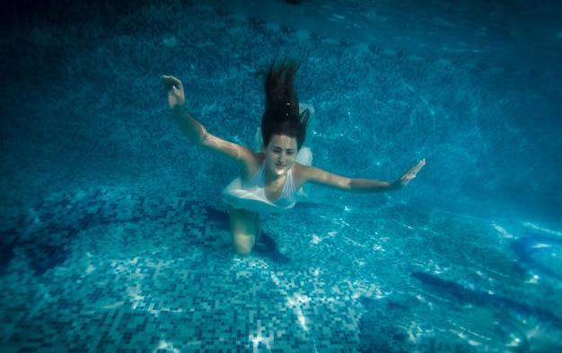 Подводный снимок женщины с длинными волосами, плавающей в бассейне