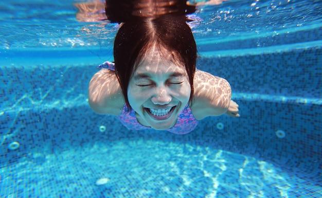 Подводный снимок молодой женщины, ныряющей в бассейн.