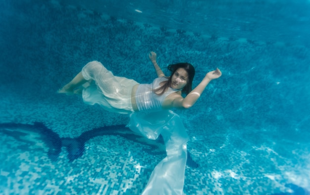 Underwater shot of woman in white cloth swimming underwater