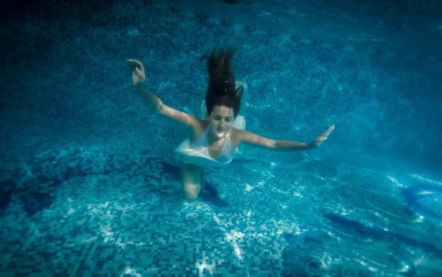 Underwater shot of woman with long hair swimming at pool