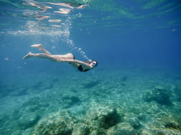 Underwater side view of attractive young cheerful girl diving with goggles and looking at the camera.