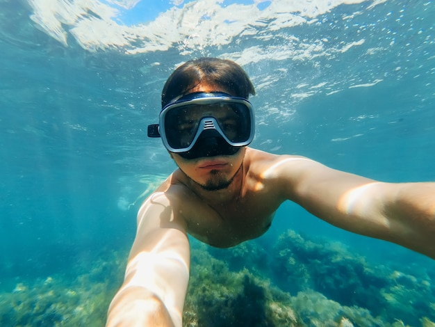 Underwater view of a diver man swimming in the turquoise sea under the surface with snorkelling mask taking a selfie