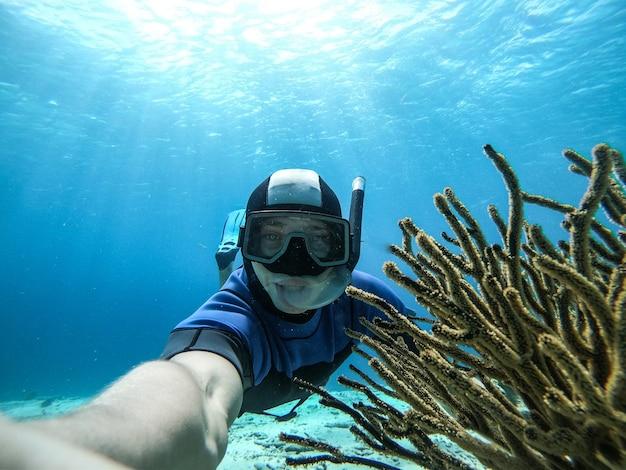Подводное широкоугольное селфи пловца в кристально чистой воде с мариной в гидрокостюме