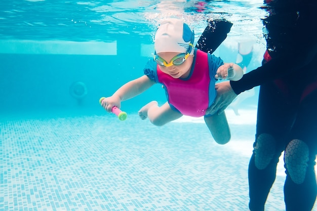 Underwater young friends in swimming pool