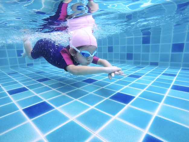 Underwater young little cute girl is swimming in the swimming pool with her swimming teacher