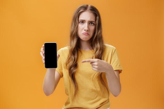 휴대폰을 가리키는 스마트폰을 보여주는 자연스러운 긴 물결 모양의 머리를 가진 불안하고 변덕스러운 귀여운 젊은 여성...