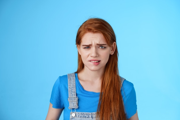 Uneasy upset redhead girl feel uncomfortable, stare frustrated, biting lip frowning, pull sad face upset, apologizing friend, express pity dilsike, stare doubtful uncertain, make bad choice