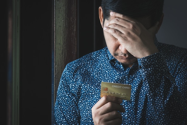 An unemployed asian man looks anxiously at his credit card during the covid-19 lockdown