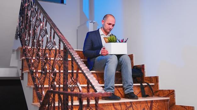 Безработный бизнесмен, сидящий на лестнице офиса в депрессии с коробкой вещей, потерял свой бизнес. группа профессиональных успешных бизнесменов, работающих в современном финансовом здании.