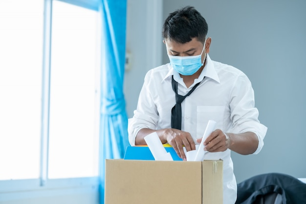 Unemployed man,businessman has a brown cardboard box and resignation letter write reason for resigning from work from the covid 19 disease situation,coronavirus has turned into a global emergency.