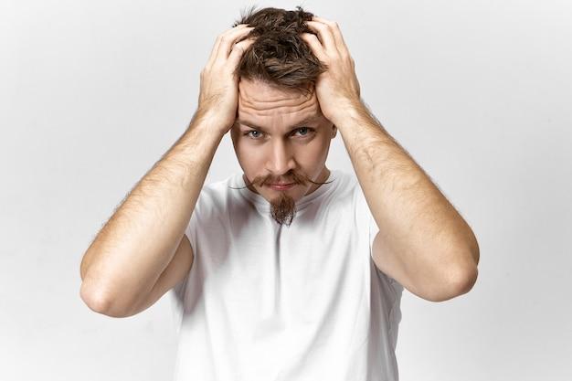 캐주얼 한 흰색 티셔츠를 입은 실업자 남자가 일자리를 찾을 수 없어 스트레스를 받고있다. 스트레스가 많은 근무일 때문에 수염과 핸들 바 콧수염이 머리를 찢는 좌절 된 젊은 남성