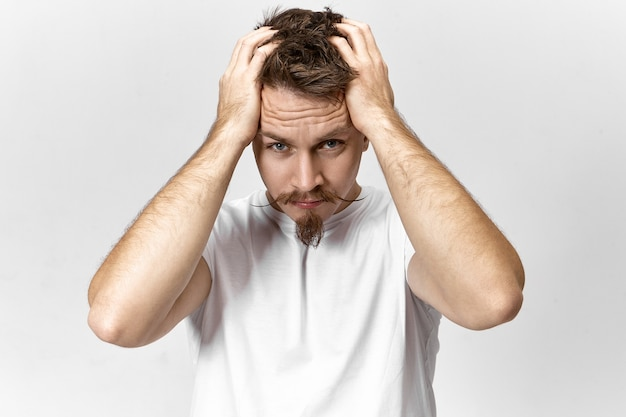Unemployed man wearing casual white t-shirt being stressed because he can't find job. frustrated young male with goatee and handlebar mustache tearing his hair out because of stressful work day