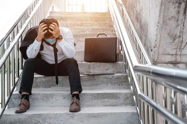 실업자는 손으로 얼굴을 덮고 있는 소송에서 젊은 아시아 사업가를 강조했습니다. 질병 covid-19, 작업 및 스트레스에 대한 실패 및 해고 개념. 사업가 절망 낮은 경제 위기