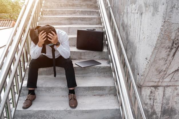 실업자는 계단에 앉아 손으로 얼굴을 덮고 양복에 노트북과 젊은 아시아 사업가 스트레스. 질병 covid-19, 작업 및 스트레스에 대한 실패 및 해고 개념.
