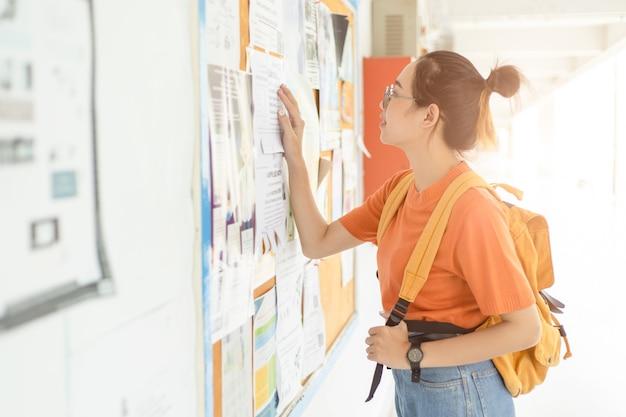포스트 보드에서 졸업 후 일이나 일자리를 찾고 있는 실업자 젊은 대학 여성
