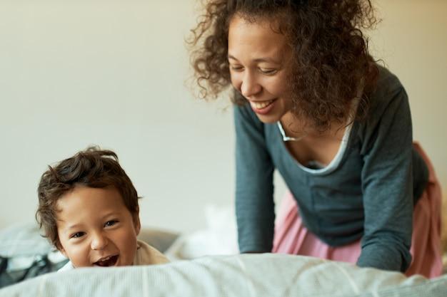 彼女の息子と一緒に楽しんで笑っている巻き毛の失業者の若い女性