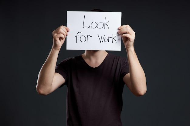 失業と危機。男は仕事を探している言葉で看板を持っています